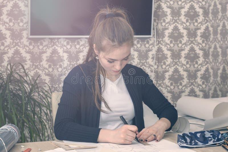 Il ritratto frontale di giovane studentessa è impegnato alla tavola disegna gli schizzi, gli schizzi, i piani, l'architettura add immagini stock libere da diritti