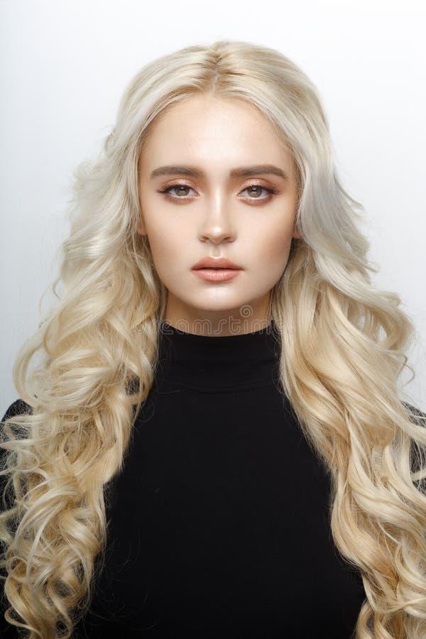 Il ritratto frontale di una ragazza bionda sveglia, con delicato compone, capelli lunghi brillanti ricci, isolati di un fondo bia immagini stock