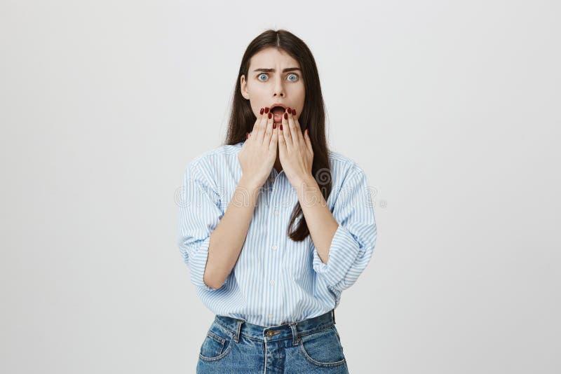 Il ritratto giovane della donna europea attraente stupita e preoccupata, stando con allarga gli occhi e dice sopra fondo grigio fotografia stock