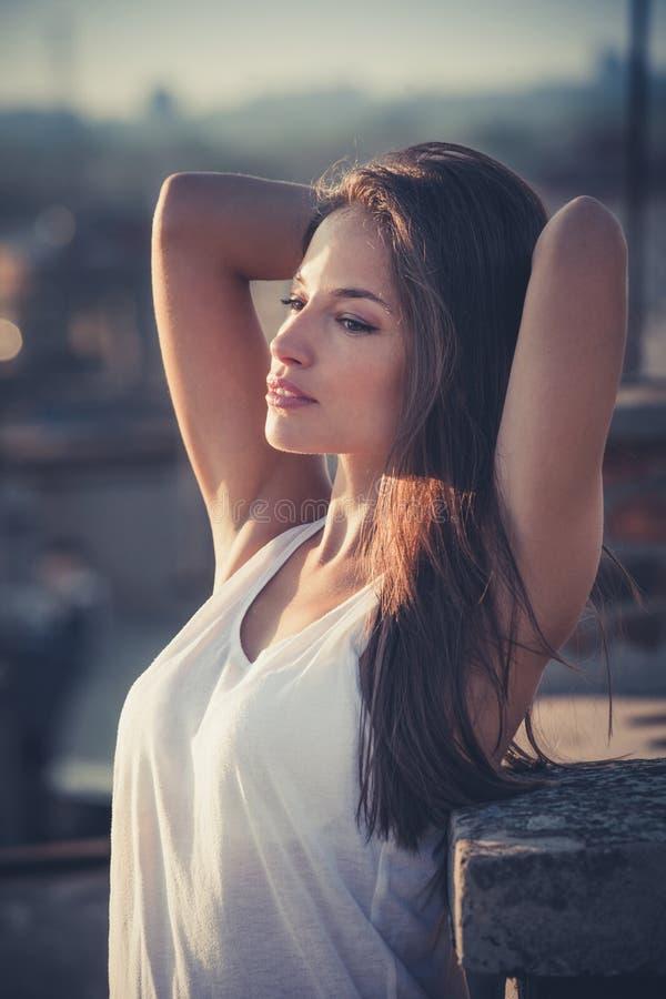 Il ritratto grazioso della ragazza della città gode di nel tramonto al tetto fotografie stock