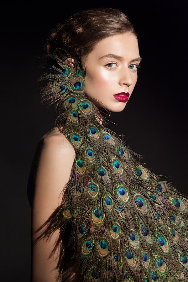 Il ritratto incredibile di bellezza di modo del modello attraente della ragazza con il pavone mette le piume a fotografia stock libera da diritti