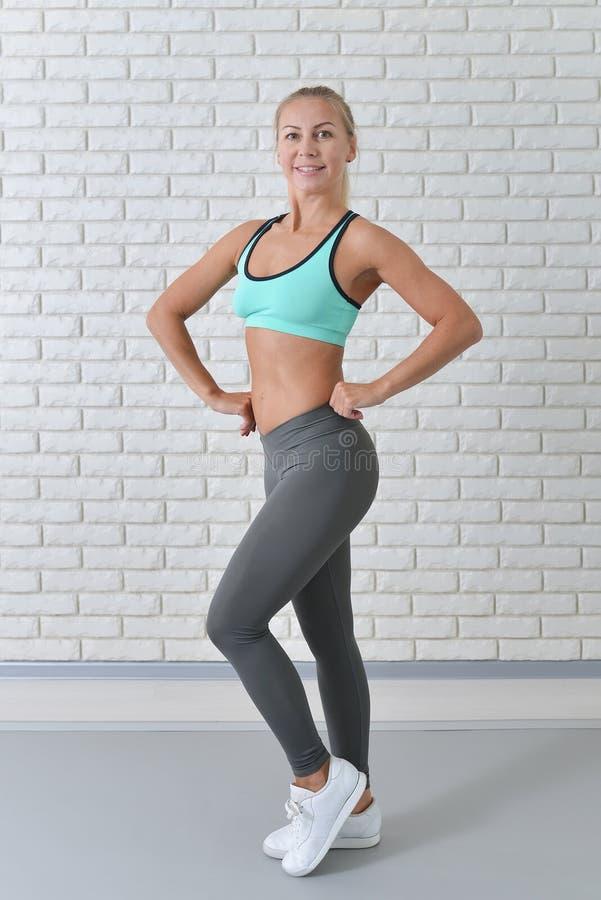Il ritratto integrale del mezzo ha invecchiato la donna di sport in abiti sportivi che posano contro il muro di mattoni bianco, m immagini stock