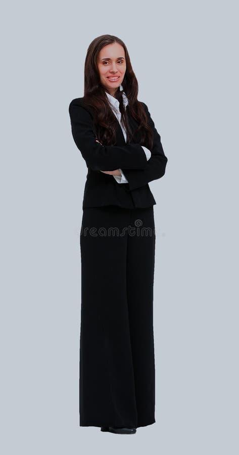 Il ritratto integrale di bella donna di affari che sta con le mani ha ripiegato il fondo bianco immagine stock