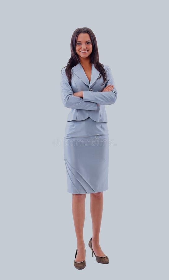 Il ritratto integrale di bella donna di affari che sta con le mani ha ripiegato il fondo bianco immagine stock libera da diritti
