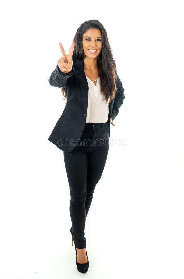 Il ritratto integrale di bella donna di affari latina che sorride e che fa sfoglia sulla condizione del segno isolato su un fondo fotografie stock libere da diritti
