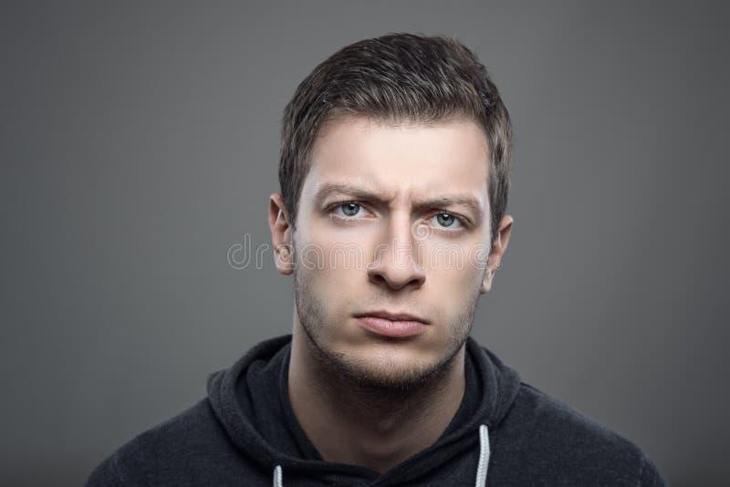 Il ritratto lunatico di colpo in testa dei giovani ha rovesciato l'uomo che esamina la macchina fotografica fotografia stock