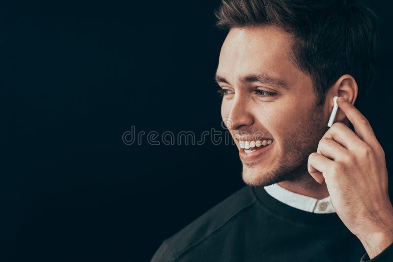 Il ritratto orizzontale del primo piano di giovane uomo bello che sorride ed ha una chiamata con un collega isolato su fondo nero immagini stock