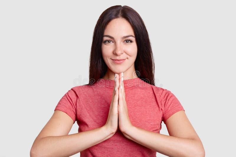 Il ritratto orizzontale della giovane donna castana fedele tiene i plams nel pregare il gesto, vestito con indifferenza, pose con fotografie stock libere da diritti