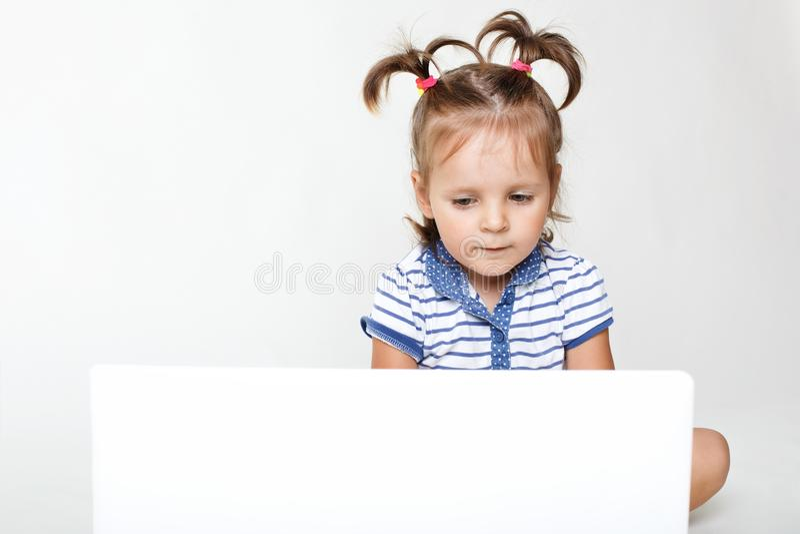 Il ritratto orizzontale di piccola ragazza graziosa messa a fuoco nel computer portatile, il fumetto interessante degli orologi o fotografie stock libere da diritti