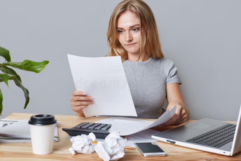 Il ritratto orizzontale di riuscita donna di affari legge attentamente le carte d'ufficio o il contratto, calcola tutto, w circon immagini stock