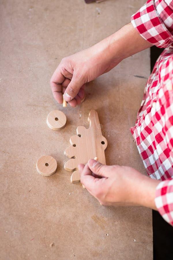 Il ritratto passa a carpentiere il giocattolo di legno del dinosauro della ruota dell'elemento a fotografia stock libera da diritti