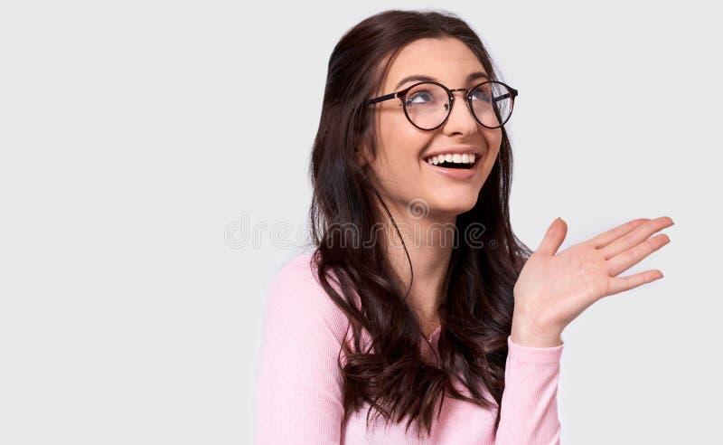Il ritratto schietto di bella giovane donna, vasto sorriso dello studio, indossa l'attrezzatura e gli occhiali casuali fotografia stock libera da diritti