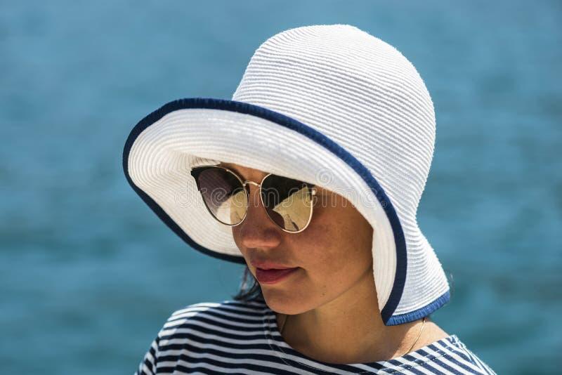 Il ritratto soleggiato di modo del primo piano della giovane donna graziosa che indossa il grande cappello elegante d'annata ed i fotografia stock libera da diritti