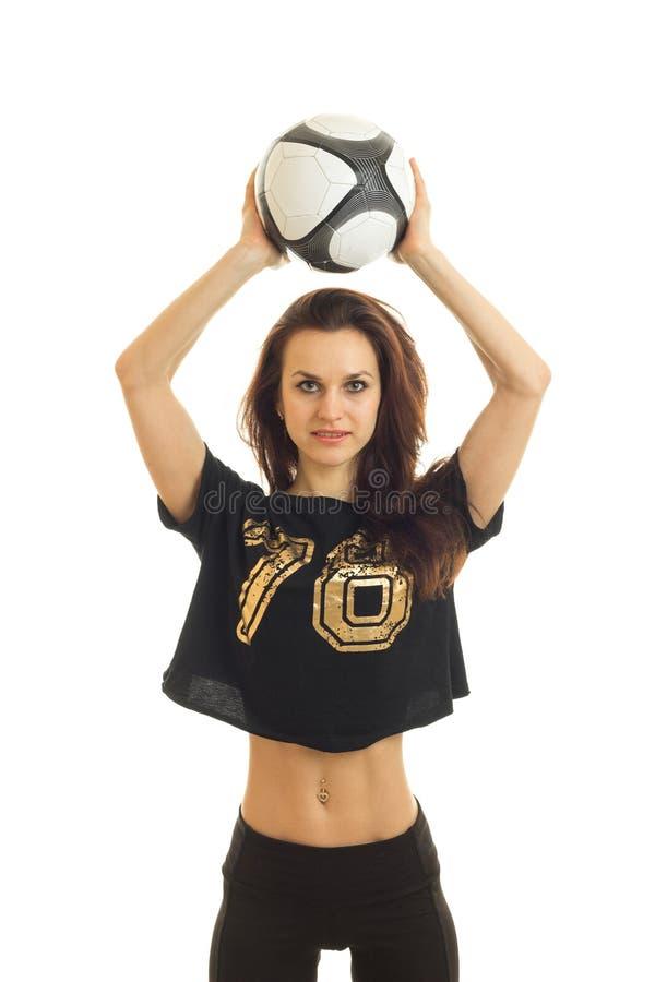 Il ritratto verticale mette in mostra una ragazza esile che tiene la testa sopra un pallone da calcio fotografie stock