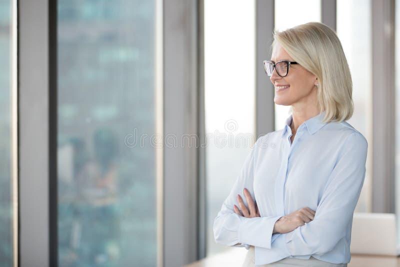 Il riuscito mezzo sorridente ha invecchiato la donna di affari che guarda attraverso la finestra immagine stock