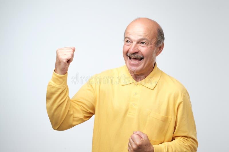 Il riuscito pensionato o uomo felice che vince, pugni di affari ha pompato la celebrazione del fondo grigio della parete di succe immagine stock libera da diritti