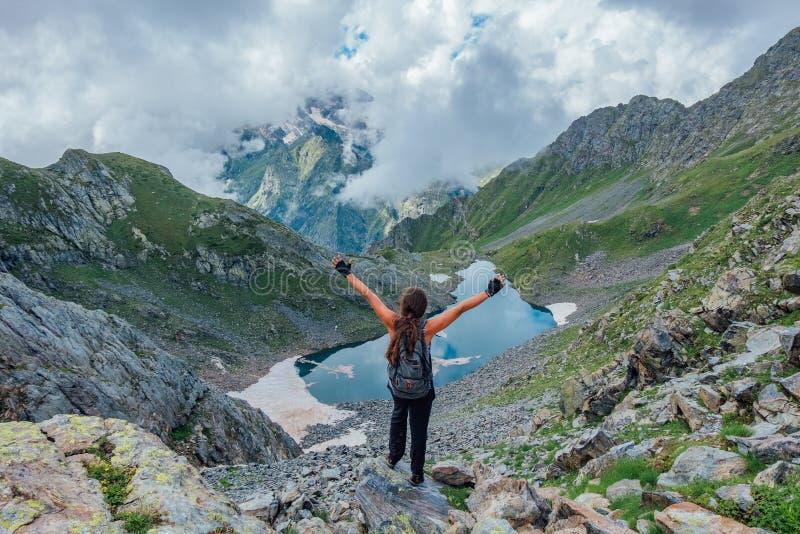 Il riuscito turista felice con il racconto del cavallino con le armi alzate su roccia alle montagne si avvicina al lago freddo de immagini stock libere da diritti