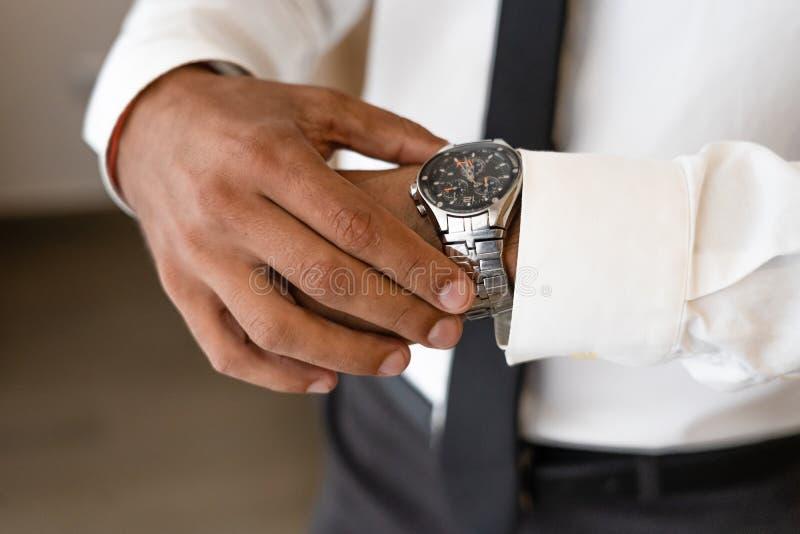 Il riuscito uomo con la camicia e la cravatta bianche considera l'orologio immagine stock libera da diritti