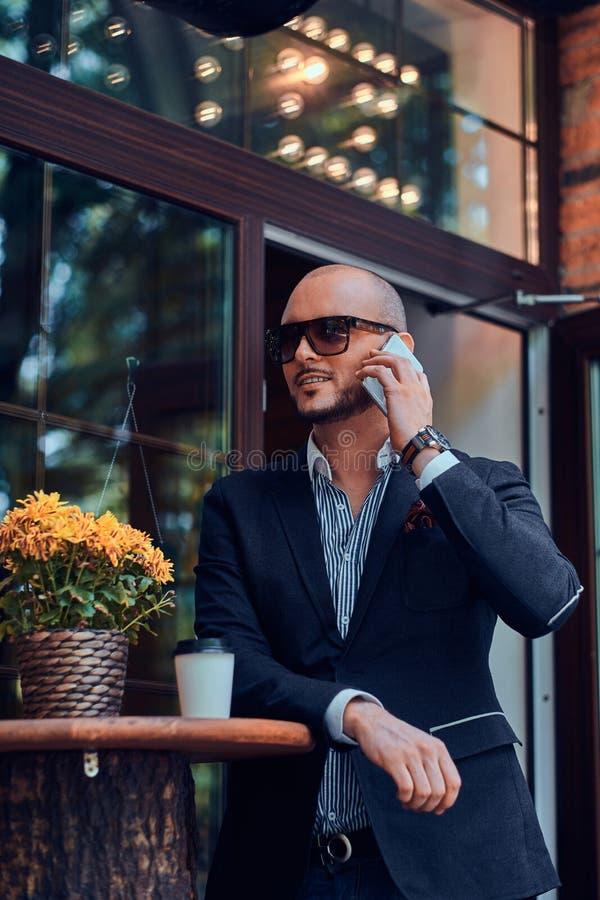 Il riuscito uomo d'affari sta parlando dal telefono mentre si sedeva al coffeeshop immagini stock libere da diritti