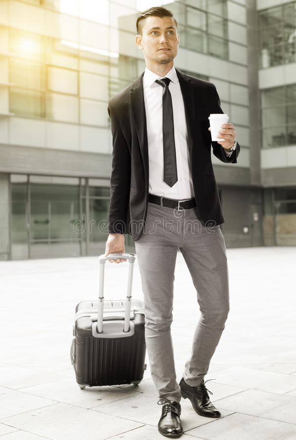 Il riuscito uomo in vestito con la valigia sta bevendo il caffè immagini stock libere da diritti