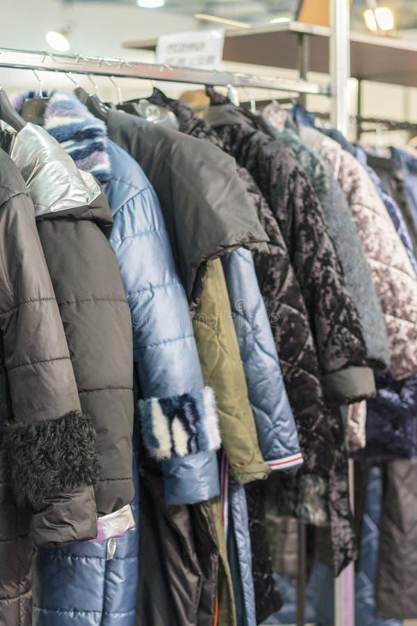 Il rivestimento dell'inverno nella vendita dell'inverno sull'vestiti tormenta I cappotti delle donne sui ganci in un negozio di v fotografia stock