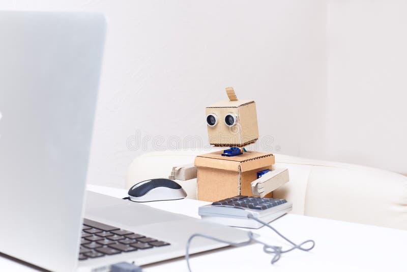 Il robot sta sedendosi alla tavola e sta funzionando ad un computer portatile fotografia stock libera da diritti