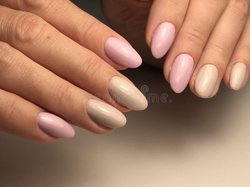 Il rosa e le unghie beige gelificano la lucidatura immagini stock