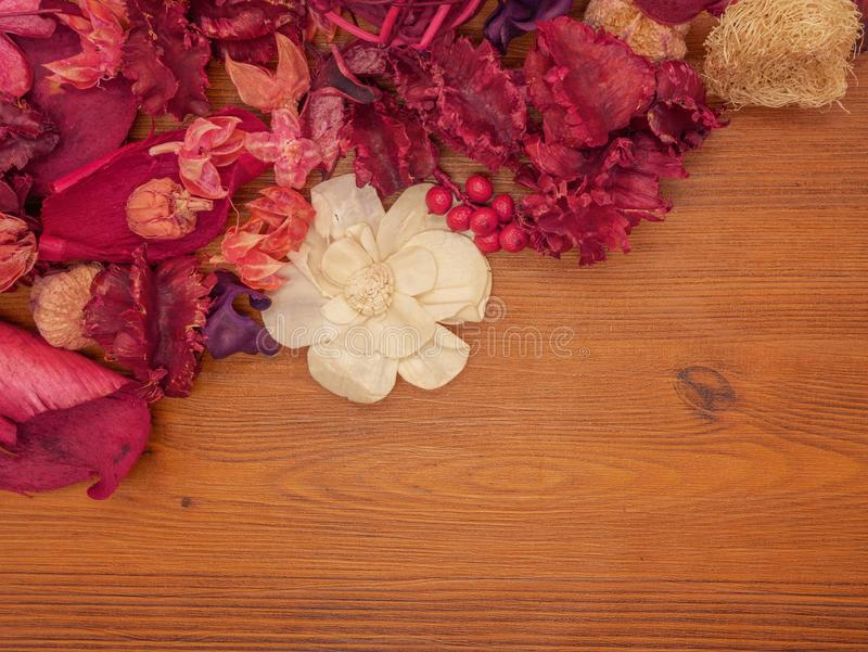 Il rosa ed il rosso di vista superiore hanno asciugato i fiori su fondo di legno marrone fotografie stock