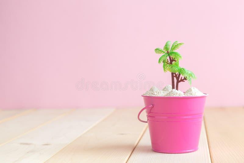 Il rosa può con la palma sullo scrittorio fotografia stock libera da diritti