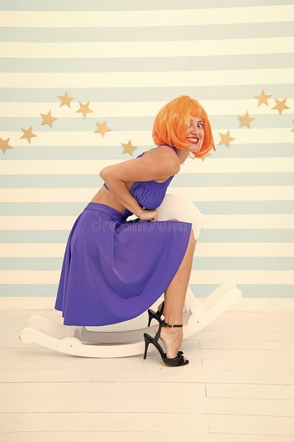 Il rosso di signora o il vestito blu dalla parrucca dello zenzero monta il cavallo a dondolo Concetto comico ed umoristico Umore  fotografia stock