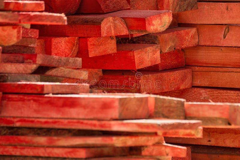Il rosso dipinto ha impilato il mucchio di legno delle barre sull'iarda mater della costruzione fotografia stock