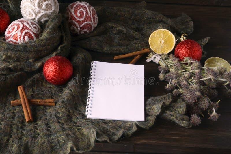 Il rosso e le decorazioni di Natale dell'oro e un blocco note per le note si trovano su una tavola di quercia Le decorazioni di N fotografia stock