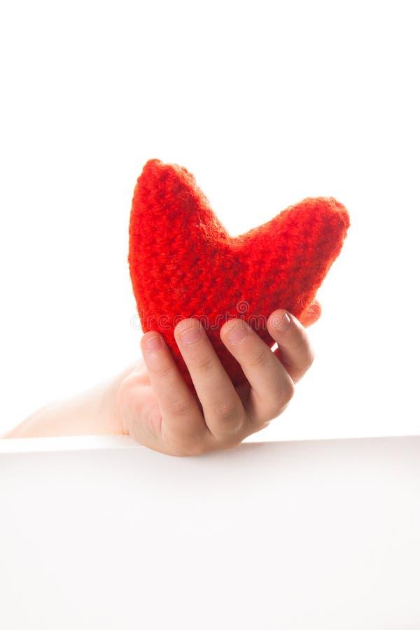 Il rosso ha tricottato il cuore nelle mani dei bambini, il concetto di Valen fotografie stock libere da diritti