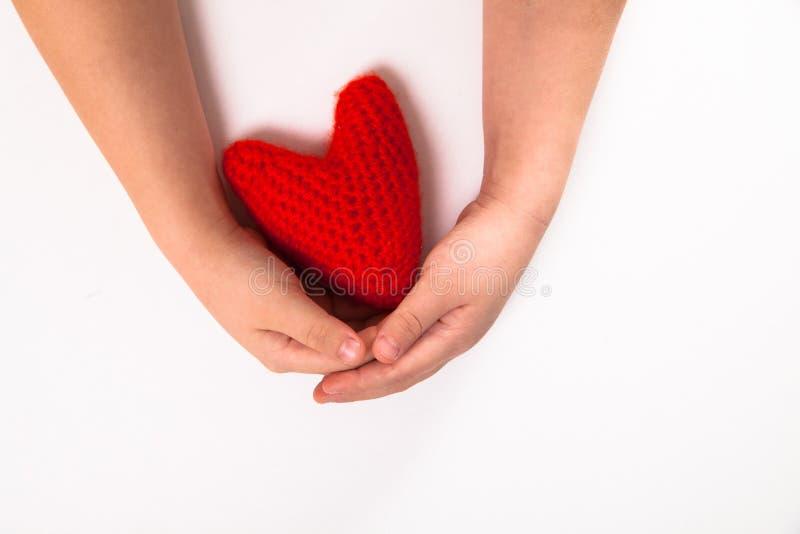 Il rosso ha tricottato il cuore nelle mani dei bambini, il concetto di Valen immagine stock