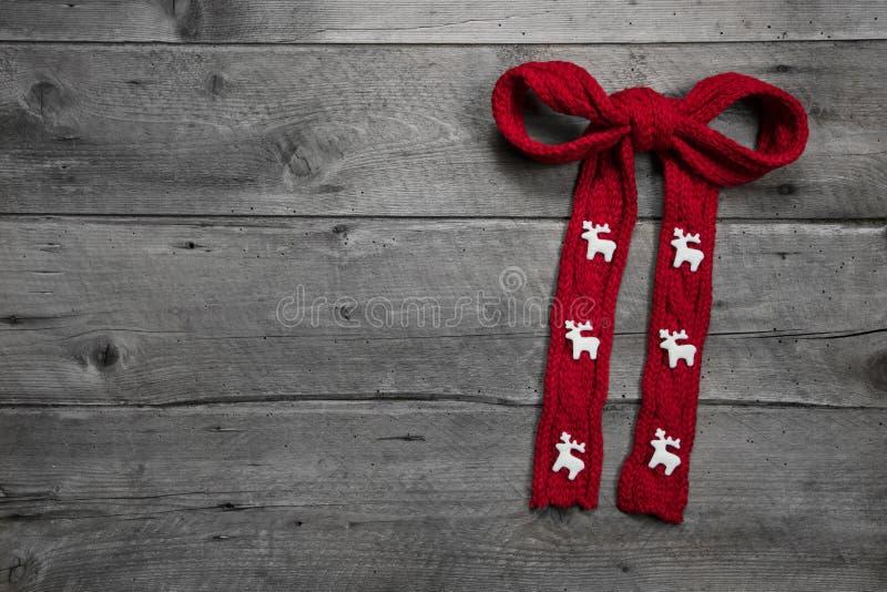 Il rosso ha tricottato l'arco con i cervi su fondo di legno per natale fotografia stock libera da diritti