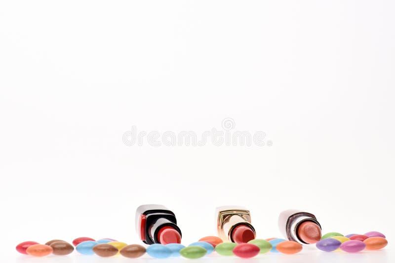 Il rosso o il color scarlatto dei rossetti si avvicina ai dolci variopinti del confetto fotografia stock