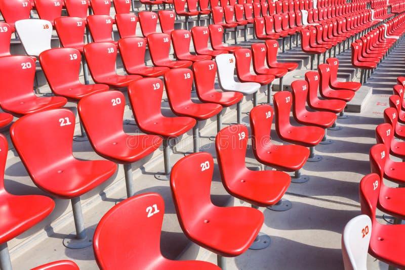 Il rosso presiede la gradinata in grande stadio immagini stock