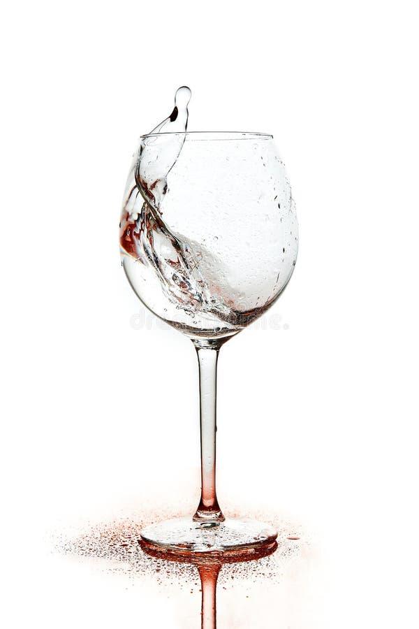 Il rosso spruzza di acqua pulita nel vetro di vino uno spruzzo di acqua Acqua potabile fotografie stock