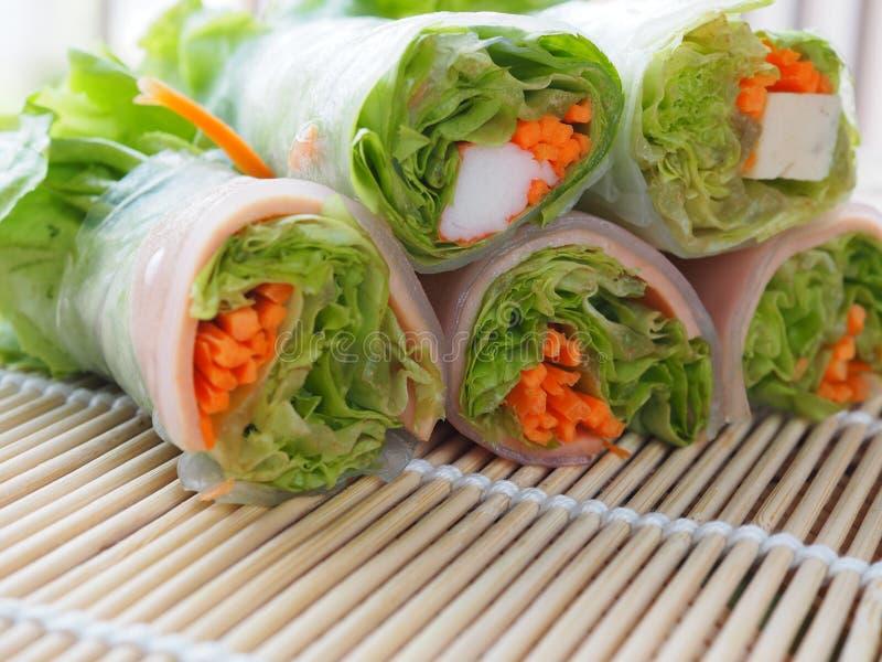 Il rotolo dell'insalata include gli ortaggi freschi, le carote, bastoni del granchio sulle fette di bambù, tessute nel contr sano immagini stock