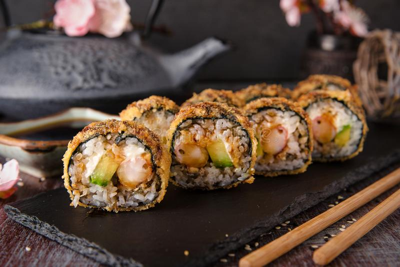 Il rotolo di sushi fritto caldo con gamberetto, il cetriolo e il unagi sauce fotografia stock