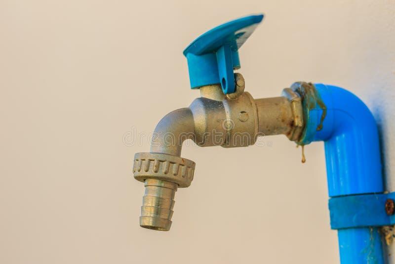 Il rubinetto bronzeo Grungy del campo si è collegato con il tubo blu del PVC nel bianco immagine stock