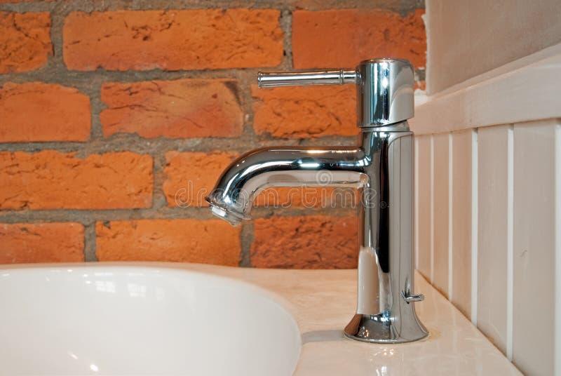 Il rubinetto con il vecchio muro di mattoni immagine stock