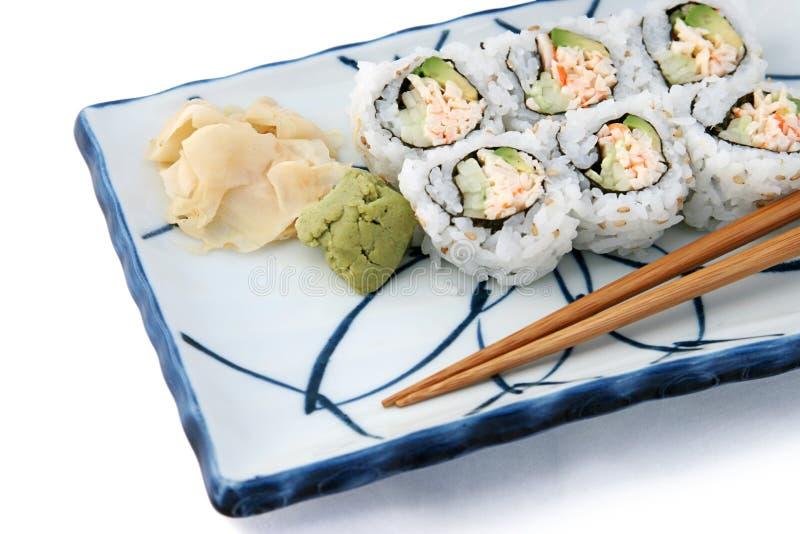 Il rullo di sushi si è inclinato su bianco fotografie stock libere da diritti