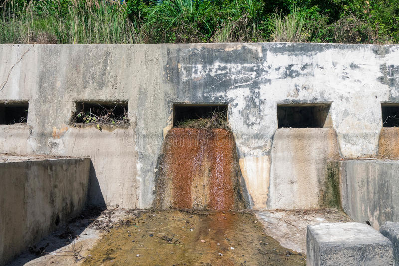 Il ruscello che attraversa un vecchio muro di cemento fotografia stock libera da diritti