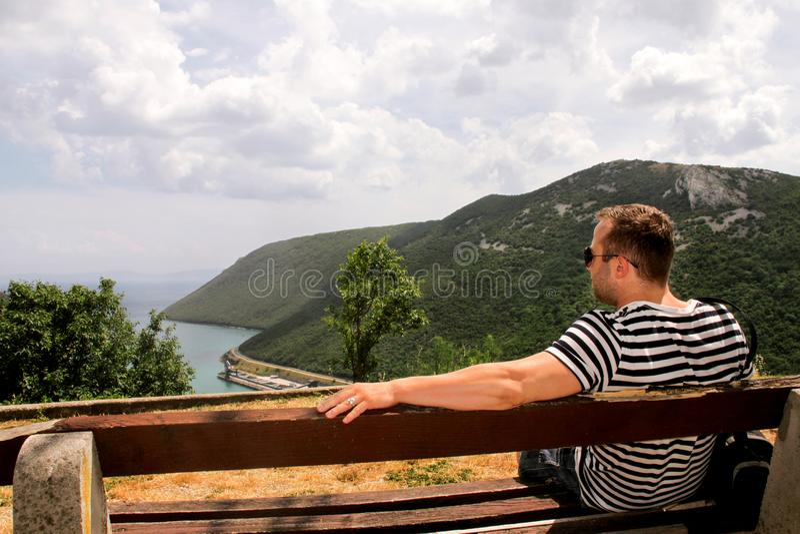 Il s'asseyant sur un banc en bois observant sur la mer et le beau s photos libres de droits