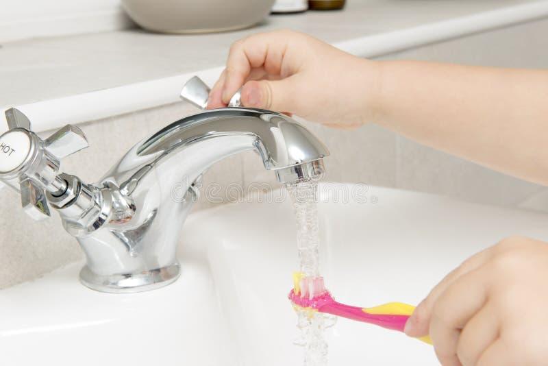 Il ` s del bambino passa lo spazzolino da denti di lavaggio sotto acqua corrente in bagno fotografia stock
