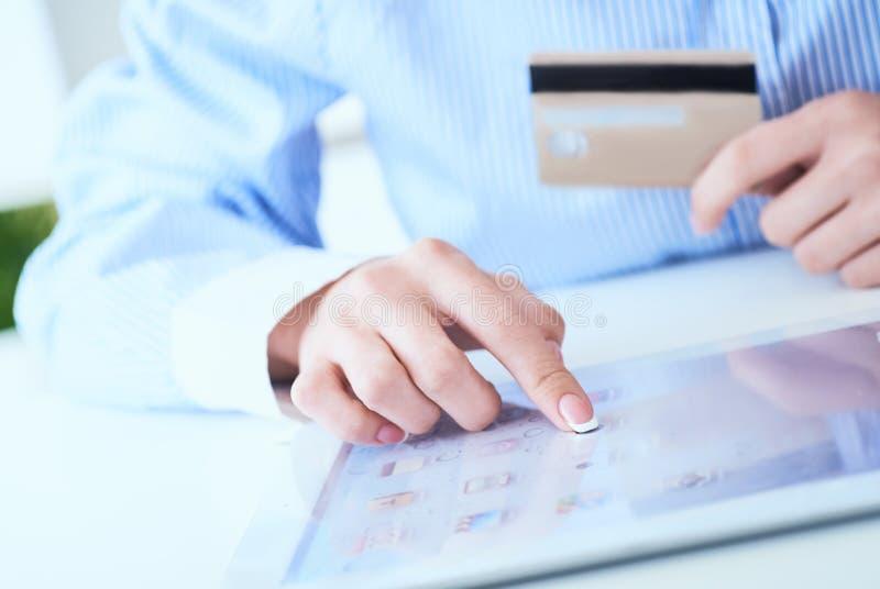 Il ` s della donna del primo piano passa la tenuta della carta di credito e per mezzo del pc della compressa per l'acquisto onlin immagini stock