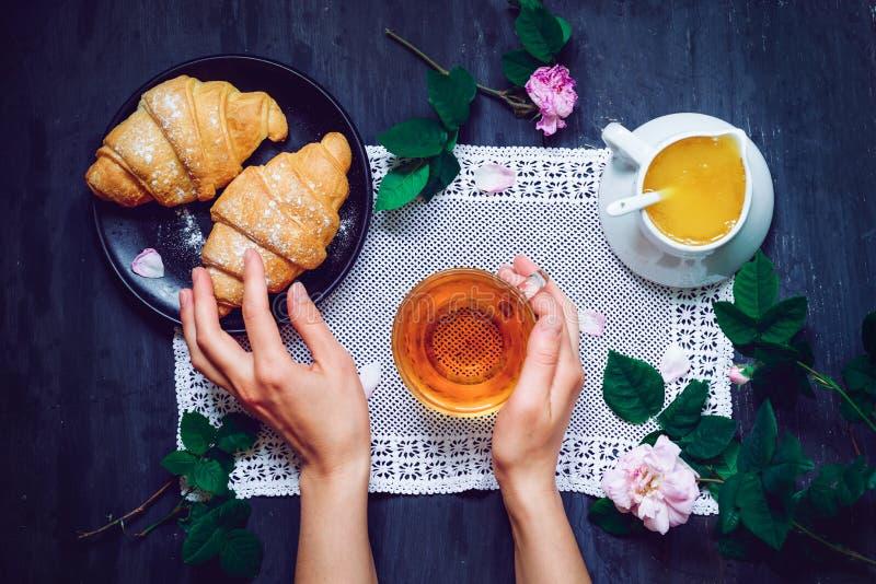 Il ` s della donna di vista superiore passa la tenuta della tazza di tè sui precedenti di legno neri con il tovagliolo d'annata,  fotografia stock libera da diritti