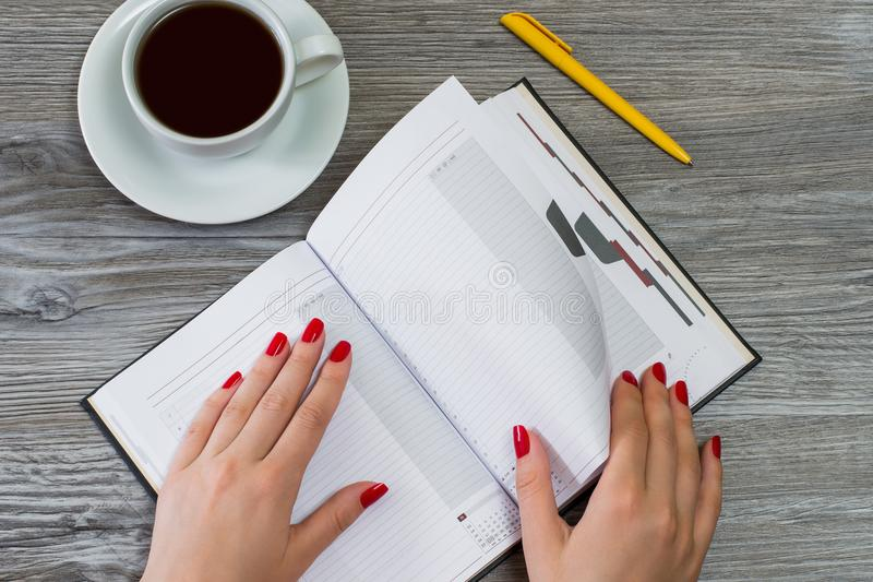 Il ` s della donna passa il giro della pagina in un taccuino Tazza di tè e di una penna fotografia stock libera da diritti
