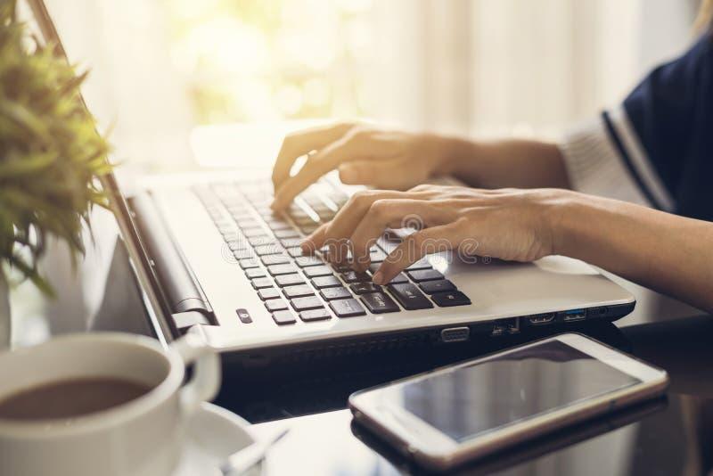 Il ` s della donna passa la battitura a macchina su una tastiera del computer portatile con la tazza di caffè fotografia stock